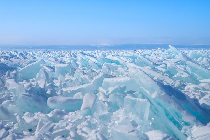 Красивые голубые шипы льда на замороженном озере с горами на предпосылке стоковые фотографии rf