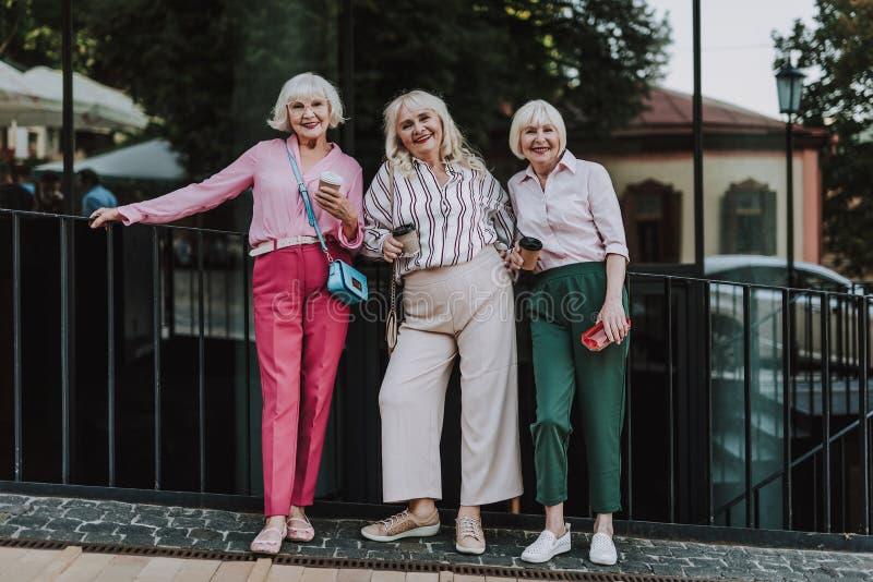 Красивые дамы стоят около черной загородки стоковое фото