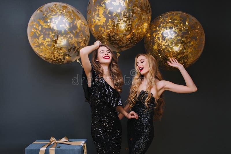 Красивые дамы танцуя с руками вверх перед светя воздушными шарами и усмехаться гелия Крытое фото уточненного коричневого цвета стоковые фотографии rf