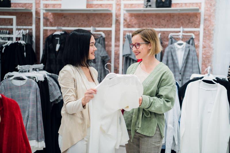 Красивые девушки выбирают одежды, говорят и усмехаются пока делающ ходить по магазинам в бутике стоковое изображение rf