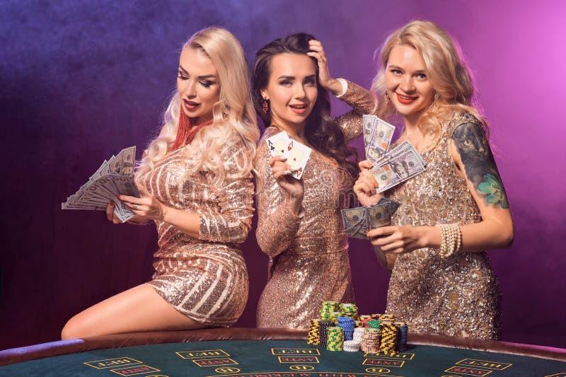 Красивые девушки с идеальные стили причесок и яркий макияж представляют положение на играя в азартные игры таблице Казино, покер стоковое фото rf