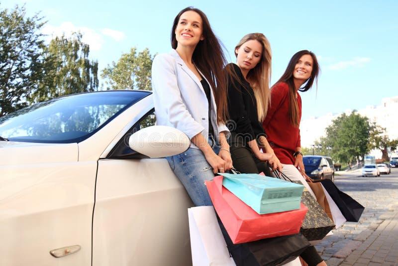 Красивые девушки с хозяйственными сумками обсуждают приобретения и усмехаются пока полагающся на их автомобиле стоковые фото
