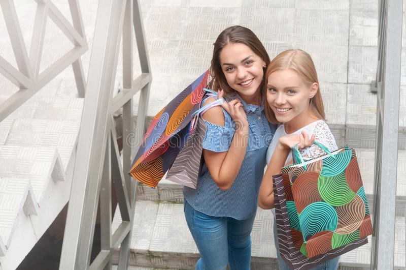 Красивые девушки с хозяйственными сумками стоят на лестницах стоковые изображения