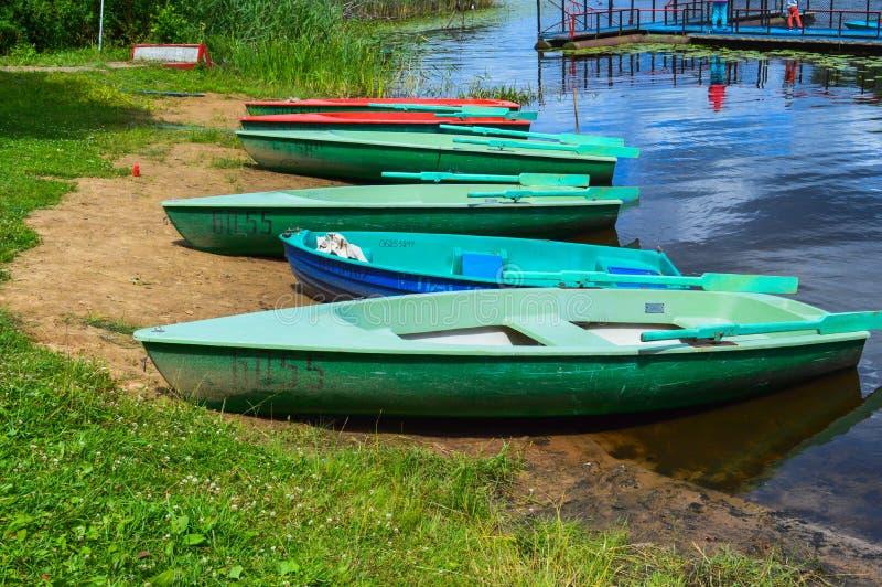 Красивые деревянные пестротканые шлюпки с веслами на пляже для прогулок вдоль реки, озера, моря, океана в природном парке стоковое фото
