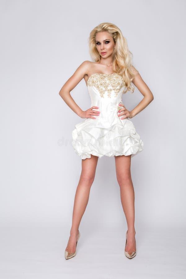 Красивые детеныши, сексуальная shapely белокурая женщина, принцесса с курчавой длинной моделью волос, невеста в белом длинном изу стоковые изображения