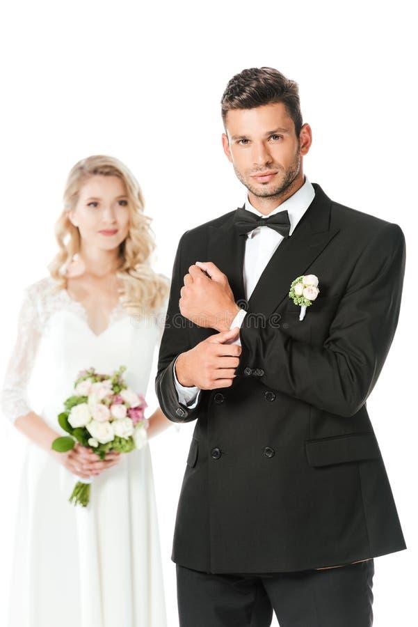 красивые детеныши холят застегивать запонку для манжет и смотреть камеру с положением невесты запачканную на предпосылке стоковые фотографии rf