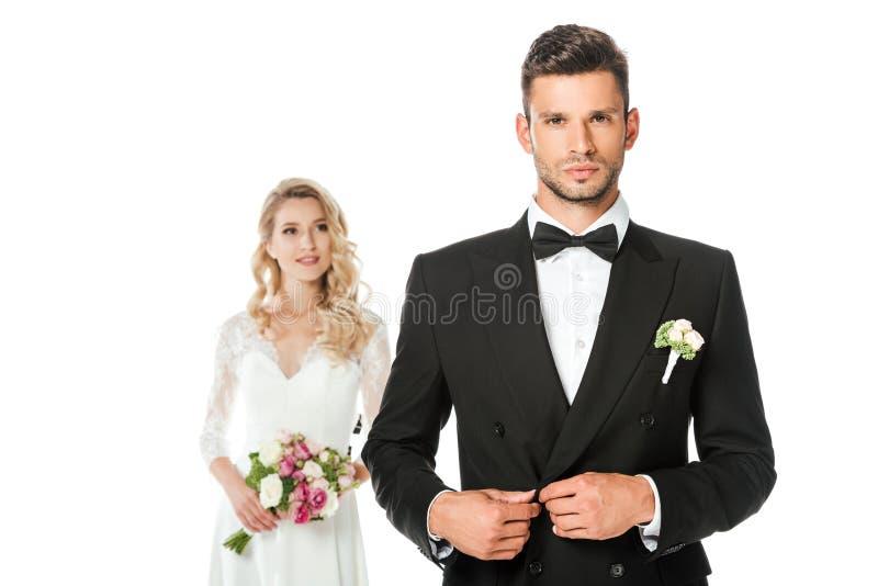 красивые детеныши холят застегивать куртку и смотреть камеру с положением невесты запачканную на предпосылке стоковая фотография rf