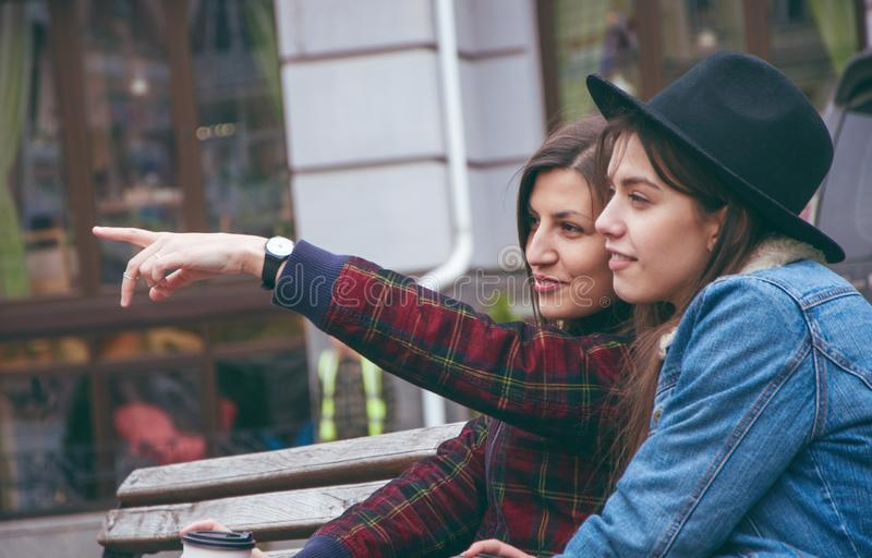 Красивые европейские девушки обсуждают что случается на стенде на заднем плане города стоковое изображение rf