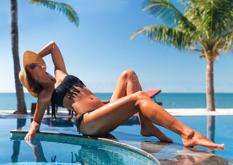 Красивые детеныши уменьшают женщину в sunbath соломенной шляпы и солнечных очков стоковое фото