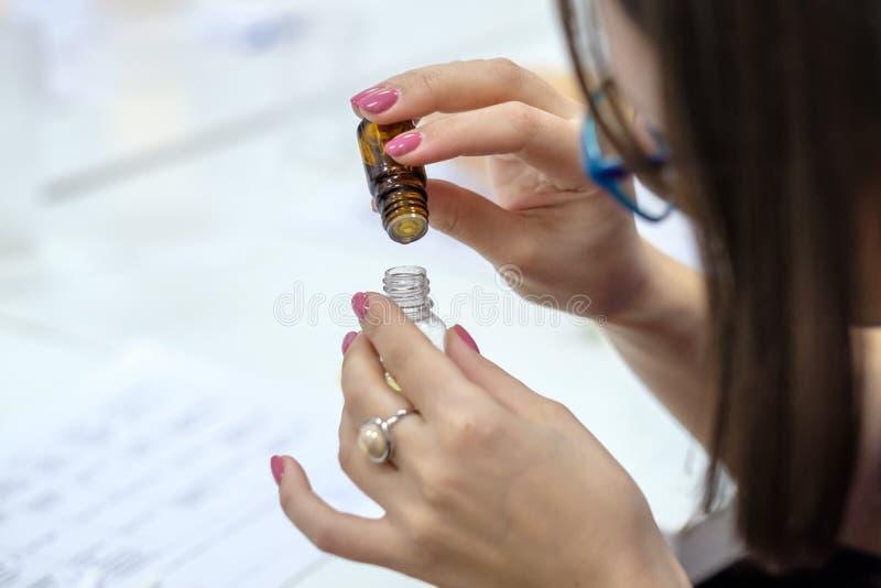 Красивые женские руки держа бутылки с эфирными маслами стоковое изображение