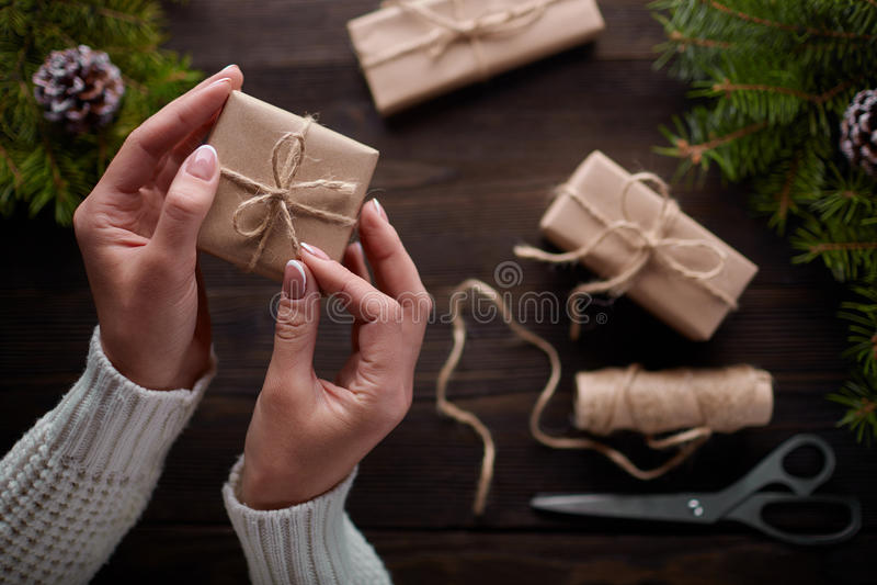 Красивые женские руки упакованный подарок рождества в коричневой бумаге kraft стоковое фото rf