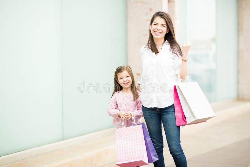 Красивые женщина и маленькая девочка с хозяйственными сумками стоковое изображение rf