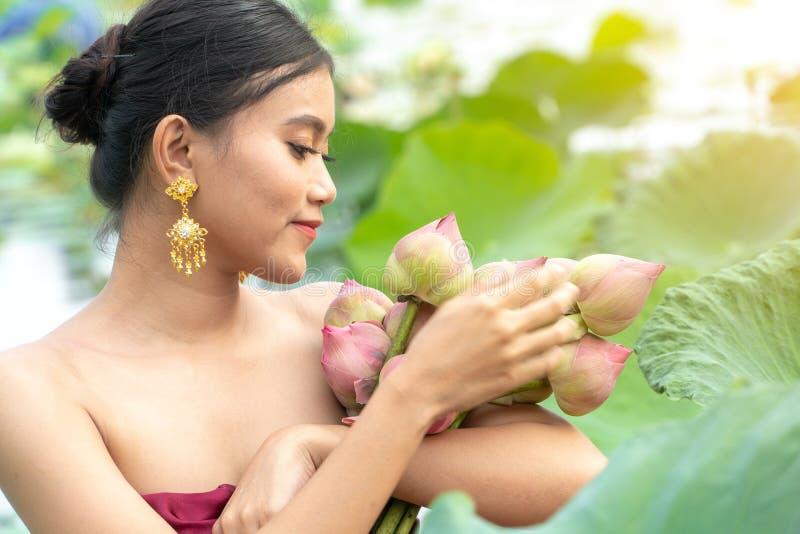 Красивые женщины Азии нося традиционное тайское платье и сидя на деревянной шлюпке в озере лотоса цветка Ее руки держат пинк стоковое фото rf