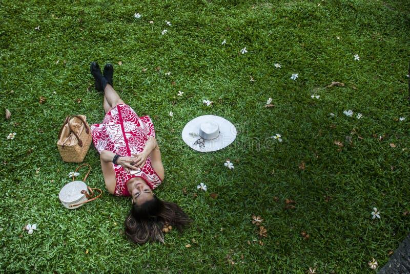 Красивые женщины наблюдая смартфоны на траве стоковое фото rf