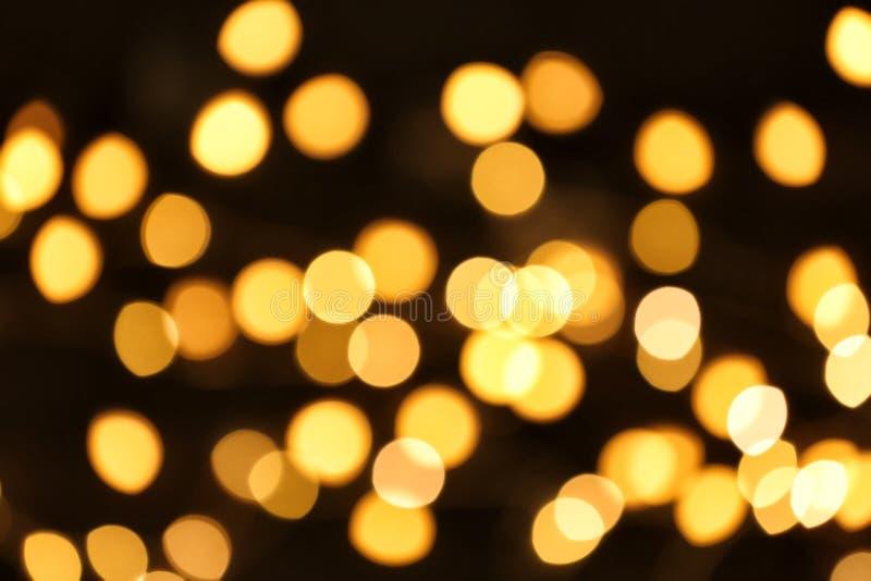 Красивые золотые света на темноте Влияние Bokeh стоковые фото