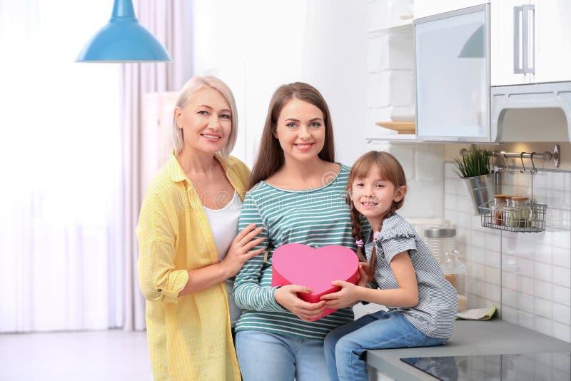 Красивые зрелые дама, дочь и внук с подарочной коробкой в кухне стоковая фотография rf
