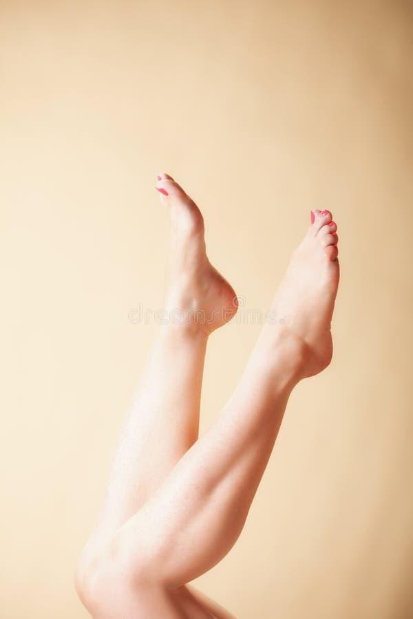 Красивые длинние нагие ноги девушки женщины на апельсине стоковое фото