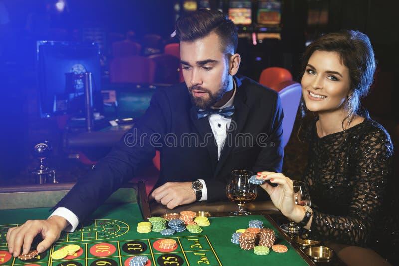 Красивые и богатые пары играя рулетку в казино стоковое изображение rf