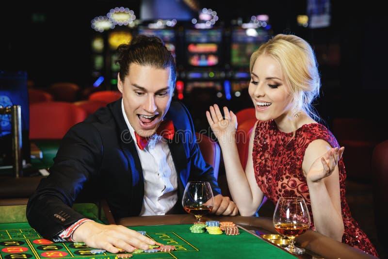 Красивые и богатые пары играя рулетку в казино стоковое фото