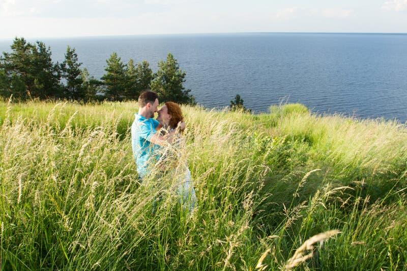 красивые любящие пары отдыхая в лете field на большой траве, лаская одине другого и целовать соедините траву стоковые фотографии rf