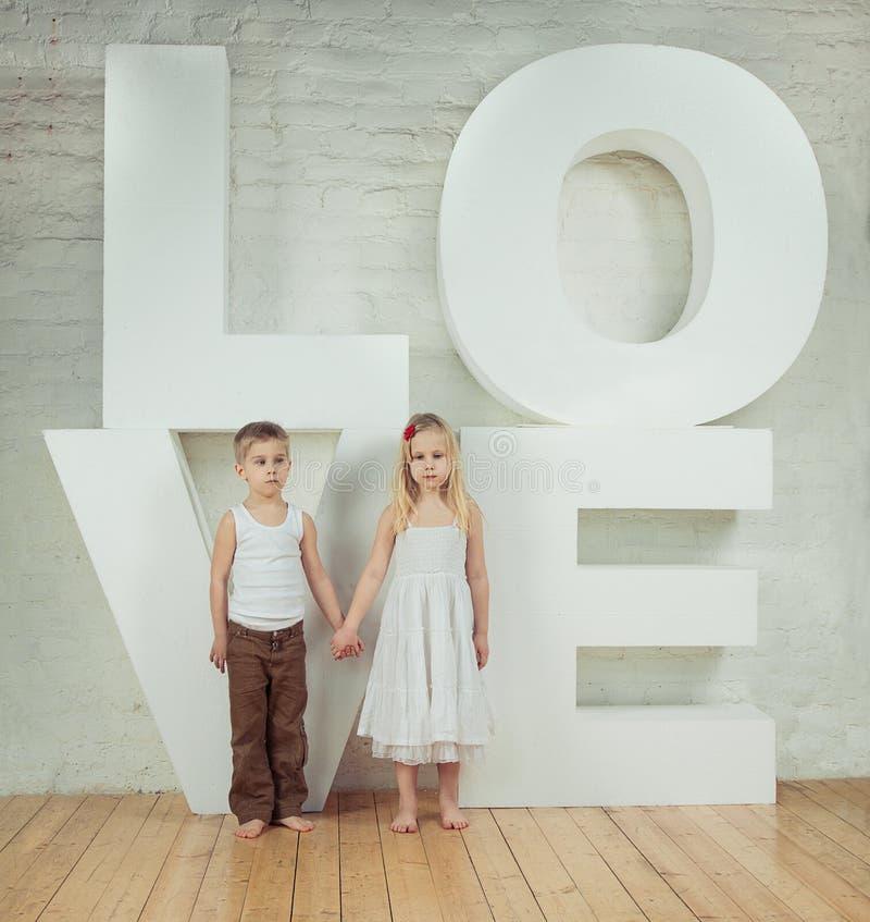 Красивые маленькая девочка и мальчик - любовь стоковые фото