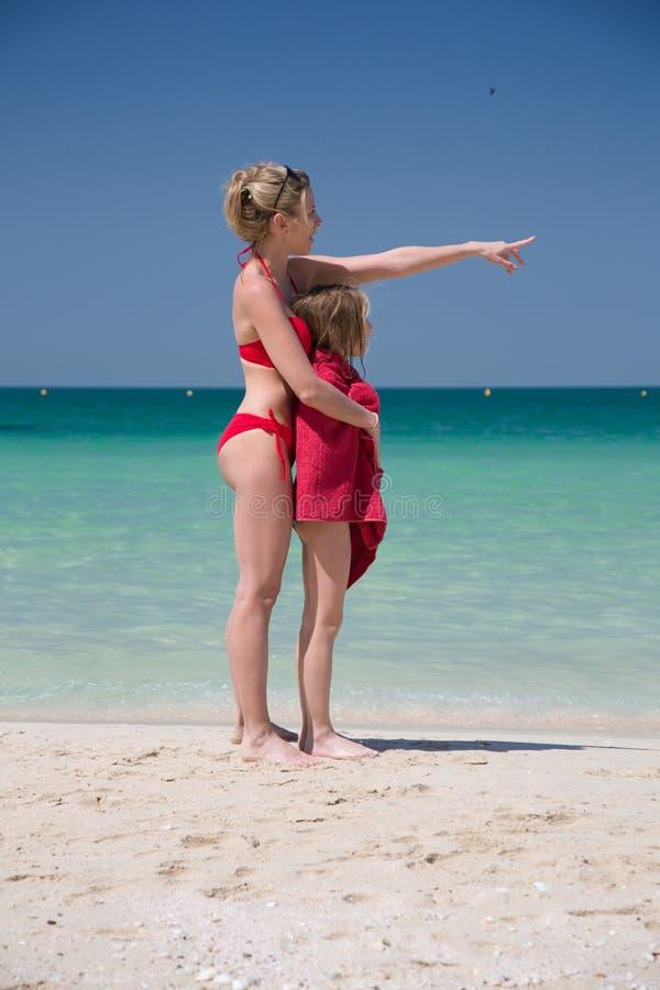 Красивые мать и дочь в красном купальнике на пляже стоковая фотография rf