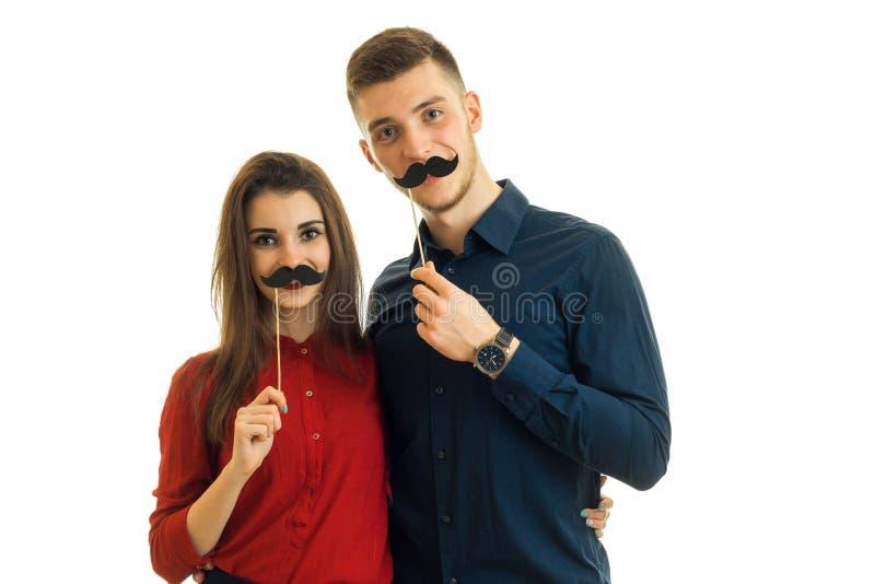 Красивые маленькая девочка и мальчик смотрят право и держат около их вискеров черноты бумаги сторон стоковые фотографии rf