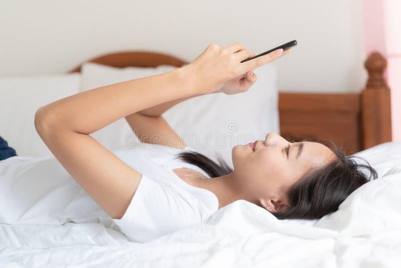 Красивые молодые азиатские женщины используют смартфон для того чтобы побеседовать с другом и звонком видео на кровати на ее доме стоковая фотография rf