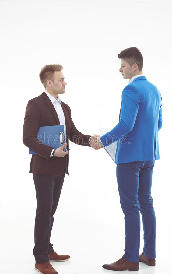 Красивые молодые бизнесмены тряся руки, стоя стоковые изображения rf