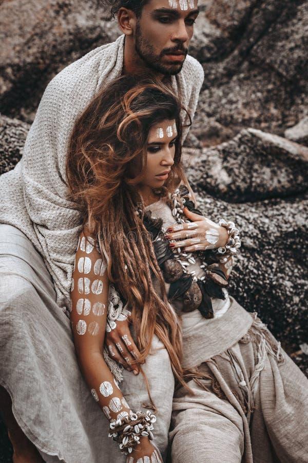 Красивые молодые дикие свободные пары в племенных костюмах на каменной предпосылке стоковые изображения rf