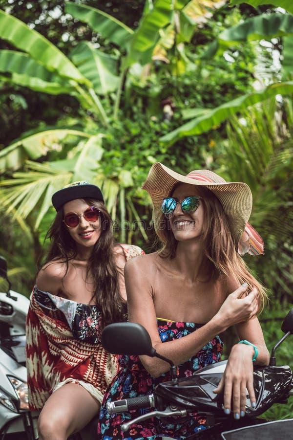 красивые молодые женские друзья в солнечных очках сидя на мотоцикле стоковые фотографии rf