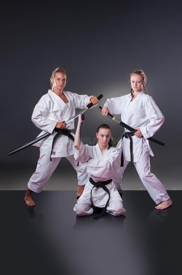 Красивые молодые женские игроки карате представляя со шпагой на серой предпосылке стоковое фото