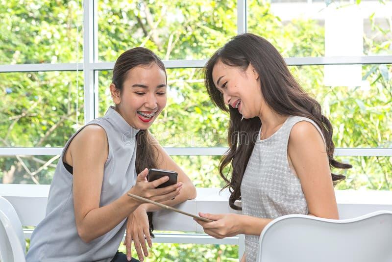 Красивые молодые женщины используя цифровые мобильный телефон и планшет в кофейне Друзья используя смартфон и планшет в баре женщ стоковое фото