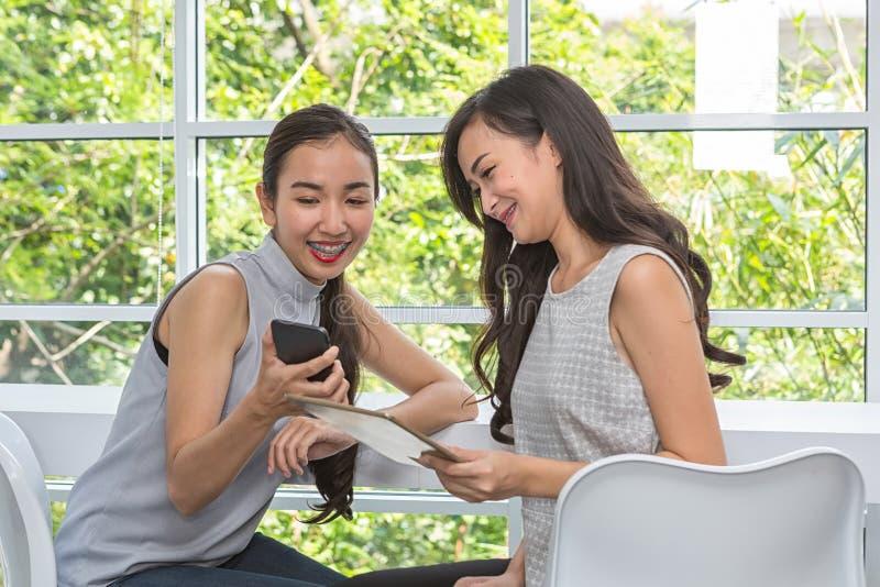 Красивые молодые женщины используя цифровые мобильный телефон и планшет в кофейне Друзья используя смартфон и планшет в баре женщ стоковые изображения rf