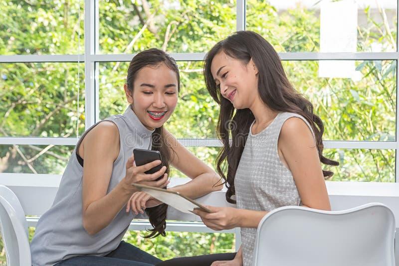 Красивые молодые женщины используя цифровые мобильный телефон и планшет в кофейне Друзья используя смартфон и планшет в баре женщ стоковые фото