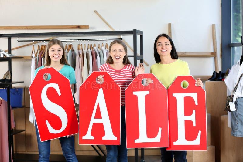 Красивые молодые женщины с большими бирками составляя слово ПРОДАЖУ в магазине одежды стоковые фото