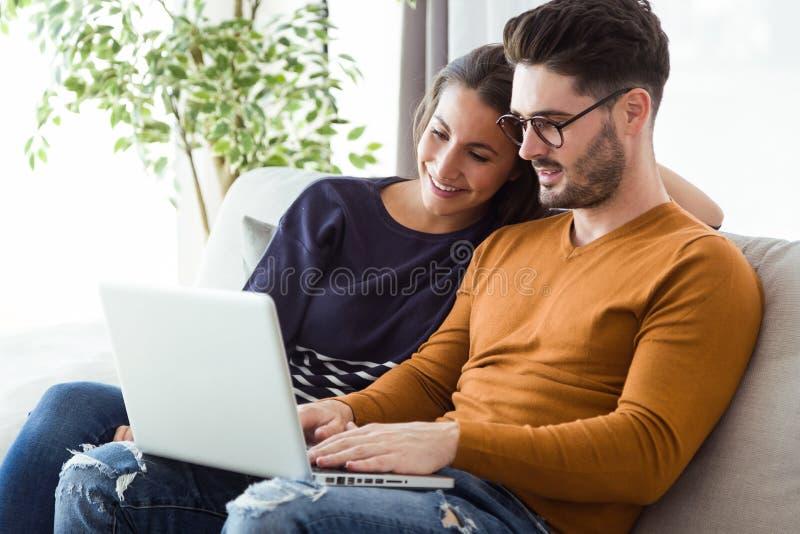 Красивые молодые пары используя компьтер-книжку на софе дома стоковое изображение
