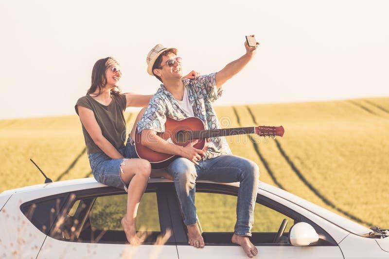 Красивые молодые пары принимая автопортрет от крыши автомобиля с умным телефоном против желтой предпосылки поля стоковое изображение rf