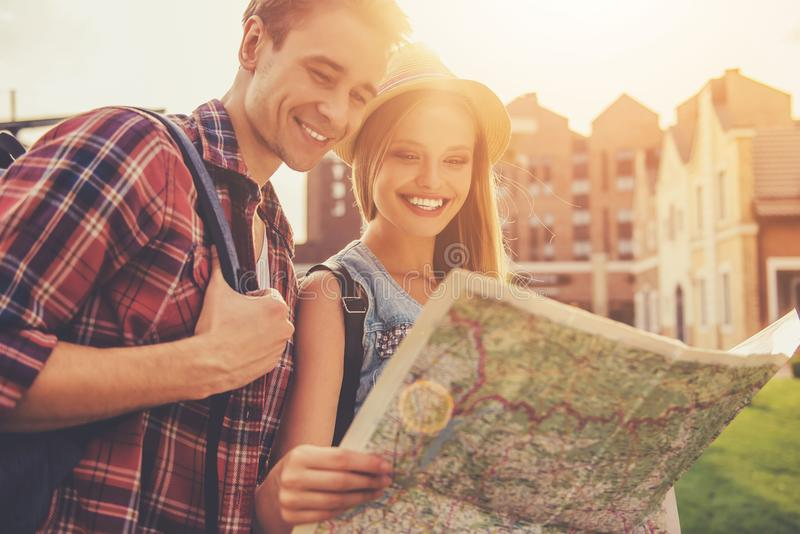 Красивые молодые пары путешественников читая карту стоковые изображения rf