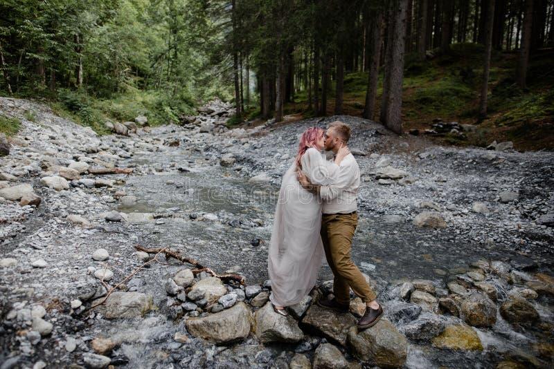 красивые молодые пары свадьбы целуя пока стоящ на утесах в быстрой горе стоковая фотография
