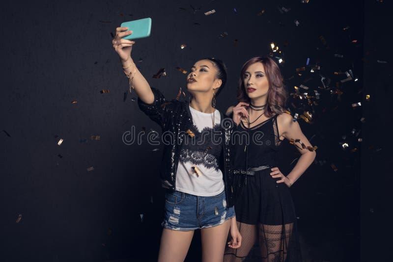 Красивые молодые стильные женщины принимая selfie со смартфоном стоковое фото rf