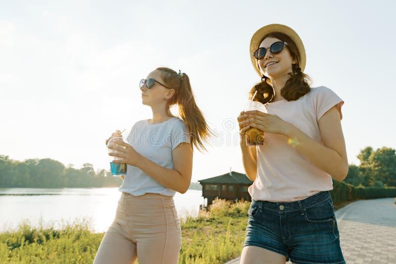 Красивые молодые усмехаясь предназначенные для подростков девушки идя на природу в парке с освежениями лета, золотом часе стоковые изображения