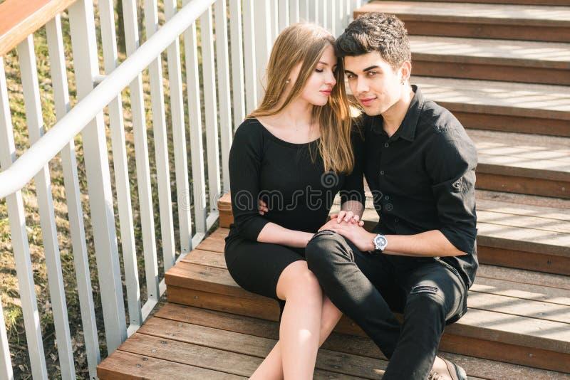 Красивые молодые multiracial пары, пары студента в любов, сидят деревянная лестница в городе Красивое турецкое объятие a парня бр стоковые изображения