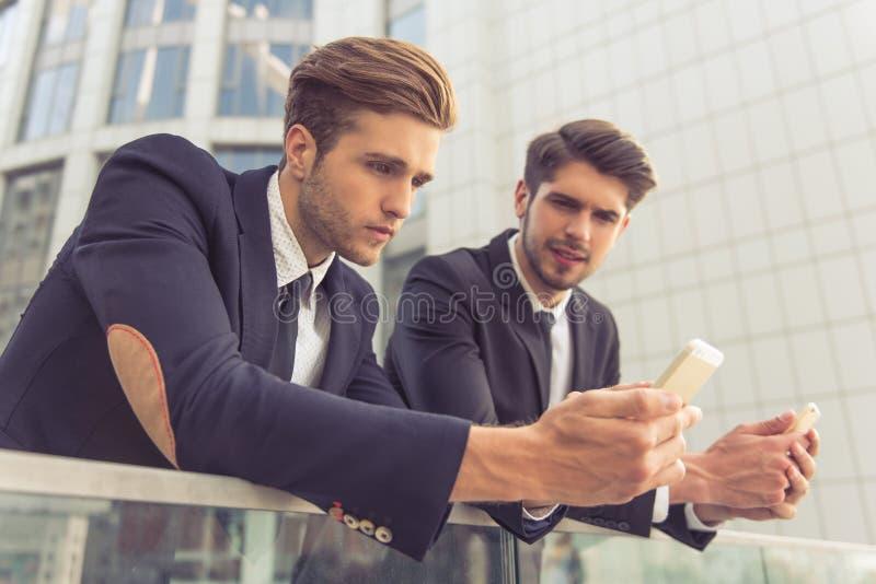 Красивые молодые бизнесмены с устройством стоковая фотография rf