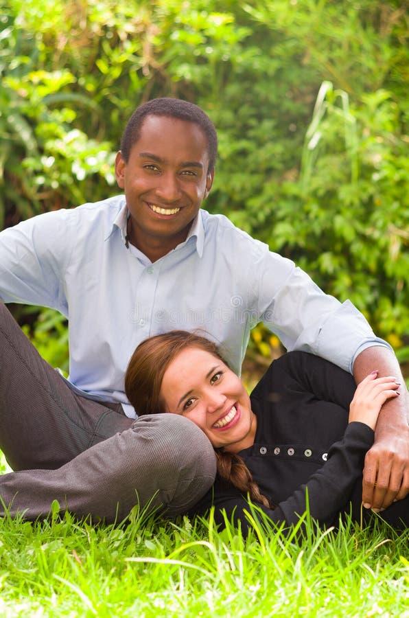 Красивые молодые межрасовые пары в сидя окружающей среде сада, обнимающ и усмехающся счастливо к камере стоковая фотография