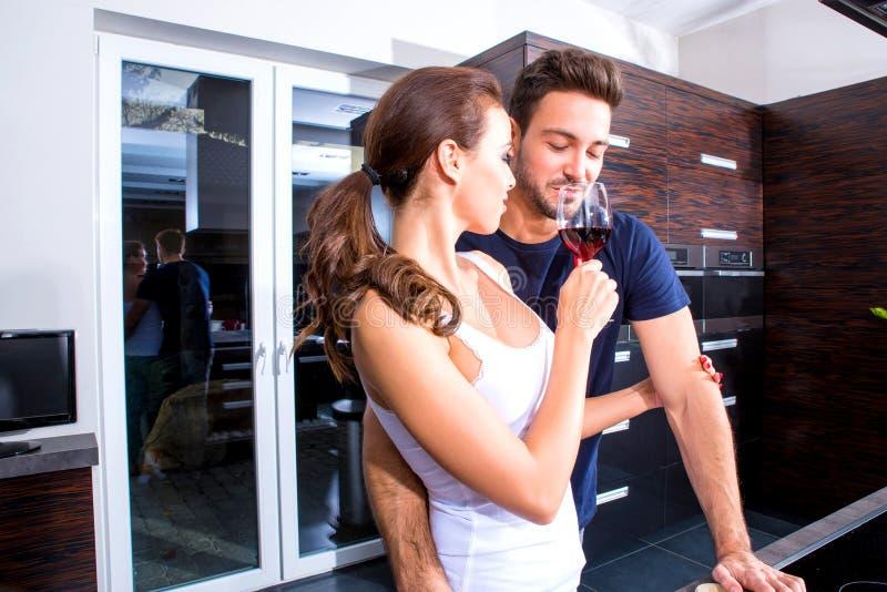 Красивые молодые пары варя пока выпивающ вино в kitche стоковая фотография rf