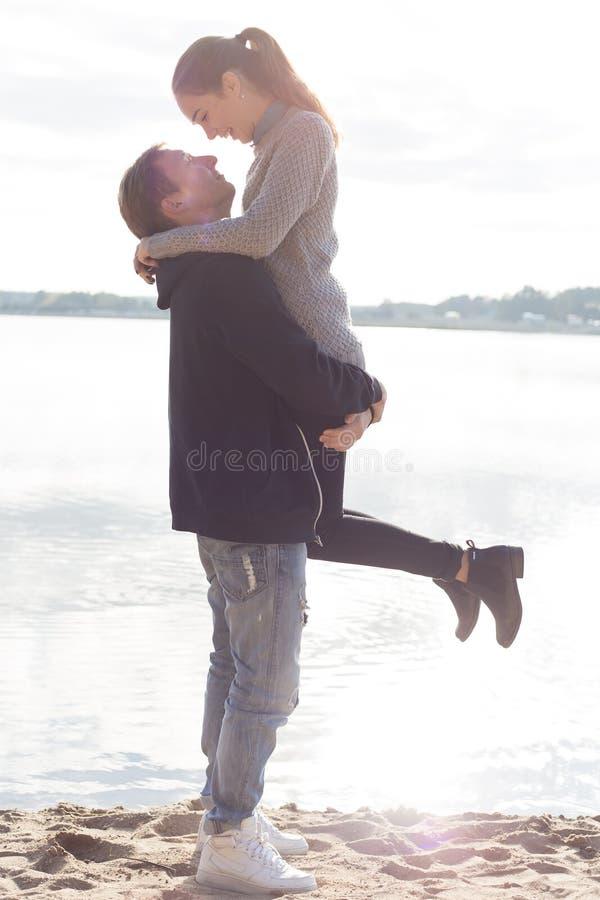 Красивые молодые пары идя вдоль пляжа на солнечной осени весеннего дня стоковое изображение rf