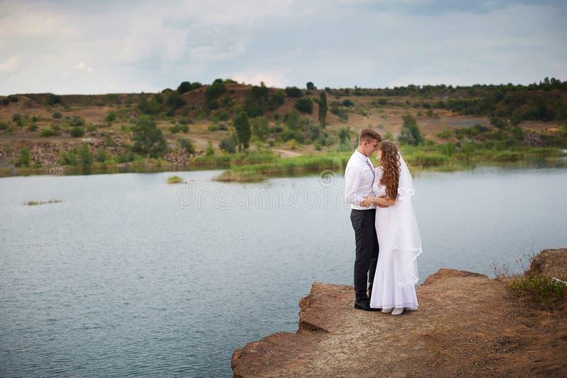 Красивые молодые пары идя около озера на день свадьбы стоковые изображения