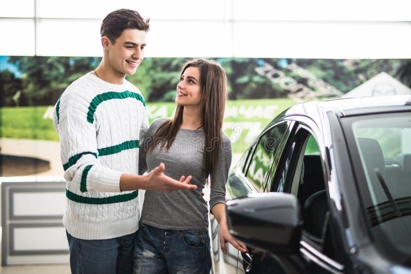 Красивые молодые пары стоя на дилерских полномочиях выбирая автомобиль для того чтобы купить Человек указанный на автомобиль стоковое изображение rf
