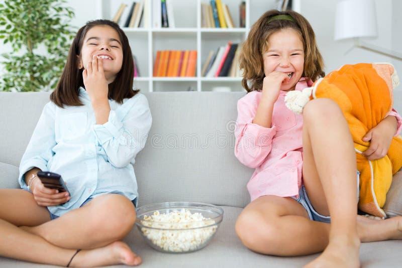 Красивые молодые сестры есть попкорны дома стоковое изображение